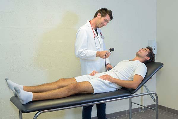 doctor in white coat examining a man wearing white